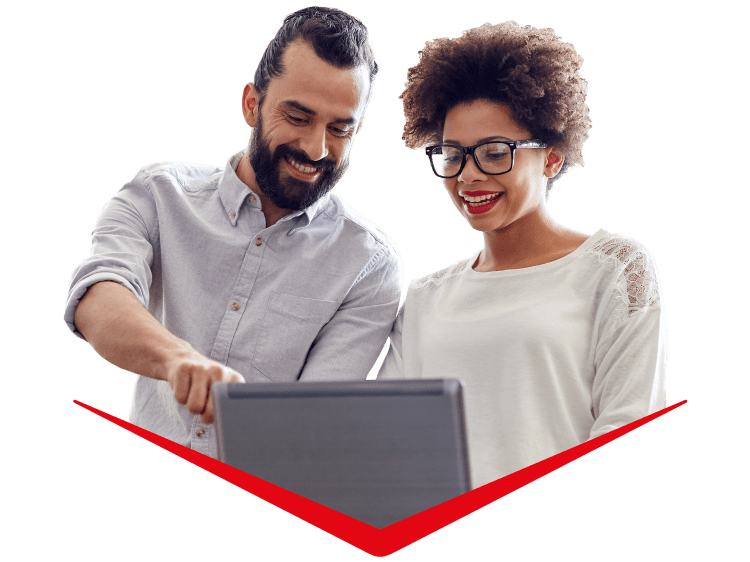 Two people looking at a computer screen together smiling, one of them pointing at something on it