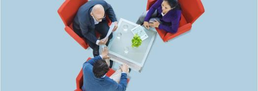 Three business people talking around coffee table