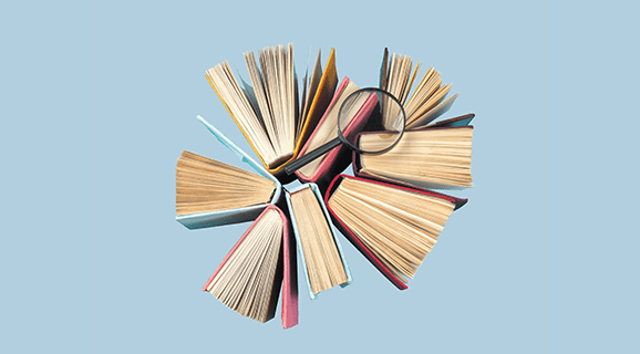Hardback books seen from above with a magnifying glass resting on them