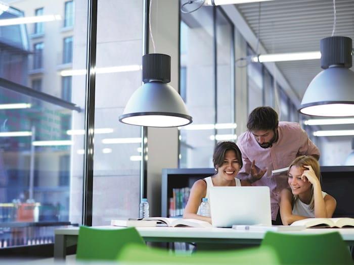 Three people huddled around desk
