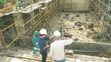 Two people in hard hats talking while pointing at parts of a construction site