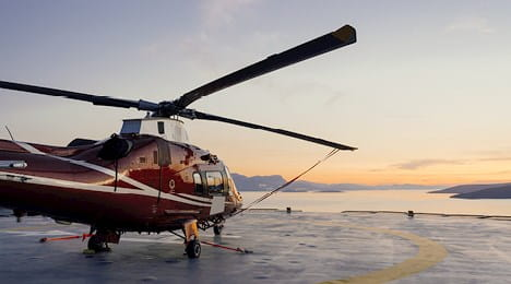 A stationary helicopter on a helipad at sunset