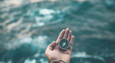 A compass in a person's hand, over water.