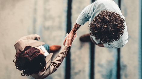 Two people shaking hands, seen from above.
