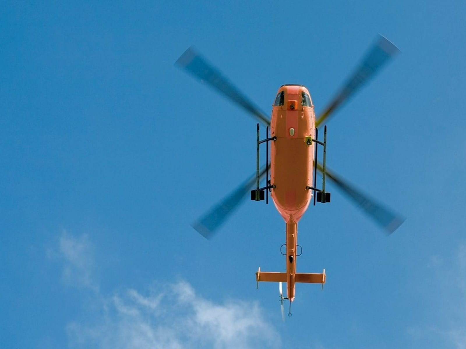 A red helicopter flying overhead.