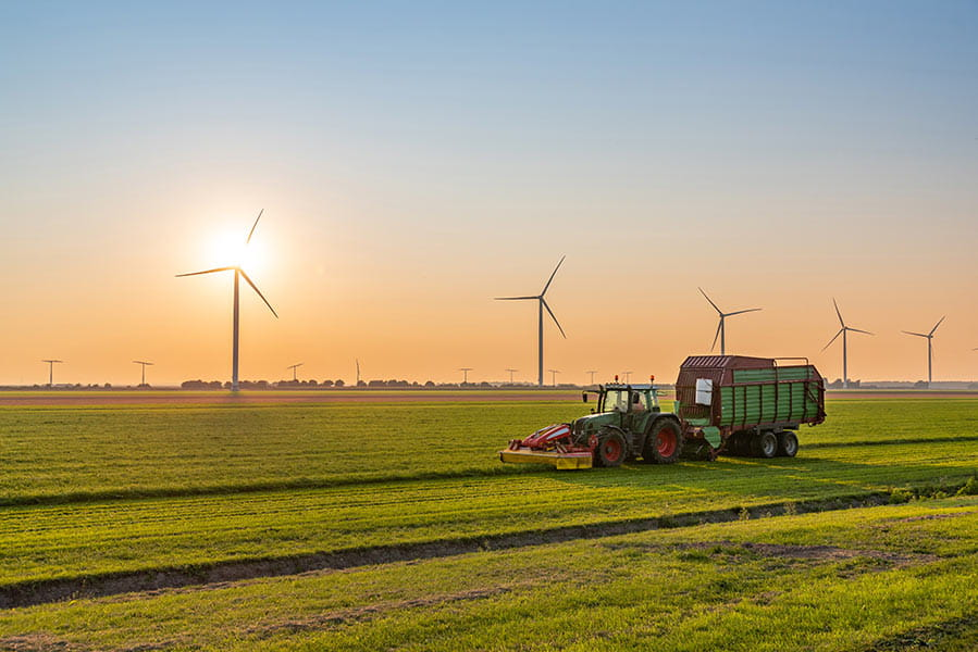 A tractor in a field with wind turbines in the distance