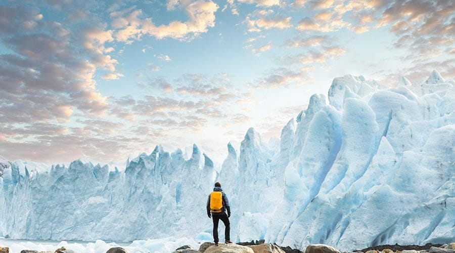 A person standing on rocks looking at a glacier