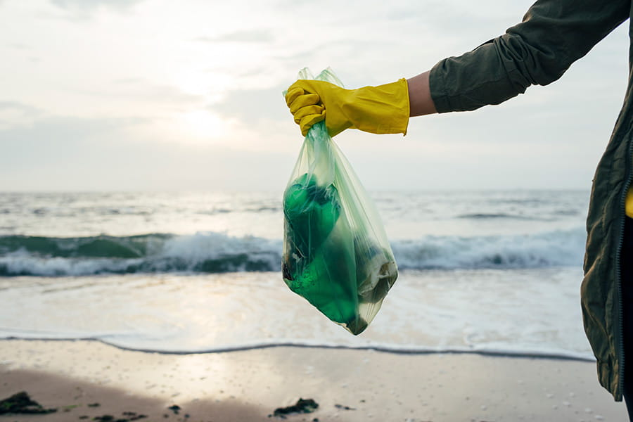 A person wearing rubber gloves standing on a beach holding a bag of rubbish