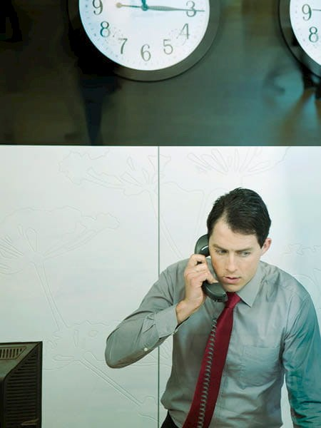 A man in business attire on a telephone with clocks on the wall above him and computer screens behind him.