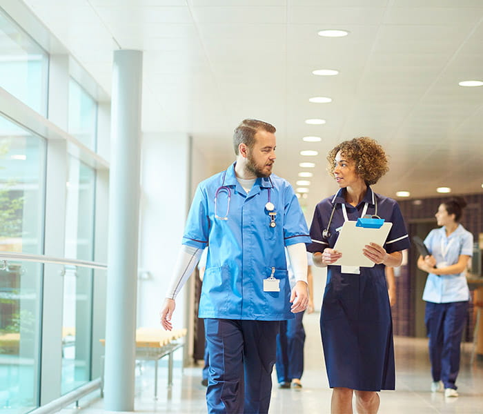 Two medical professionals walking and talking in a hospital corridor