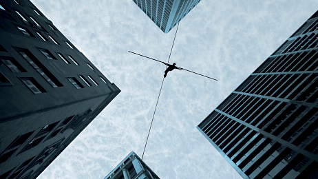 Person walking a tight rope between skyscrapers