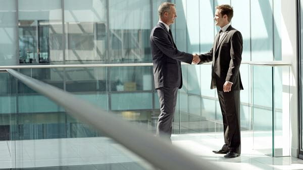 Two business people shaking hands in an office building