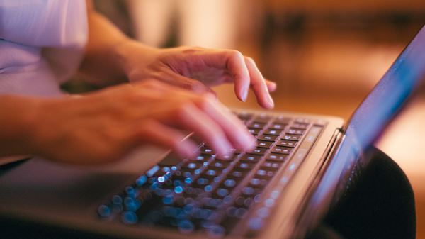 Hands typing at a laptop