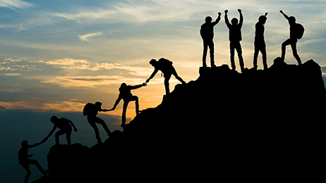 People helping each other up a hill