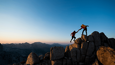 Two people scaling a peak, one helping the other up