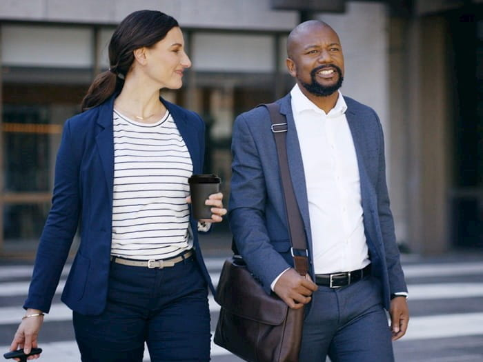 Two people in business attire walking outside together