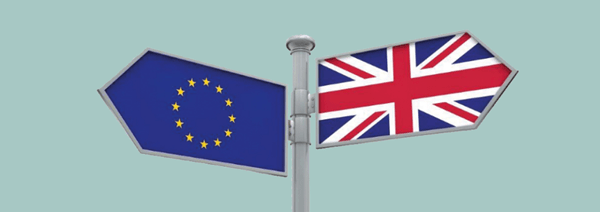 A signpost with an EU flag on one side and a Union Jack on another, pointing in different directions.