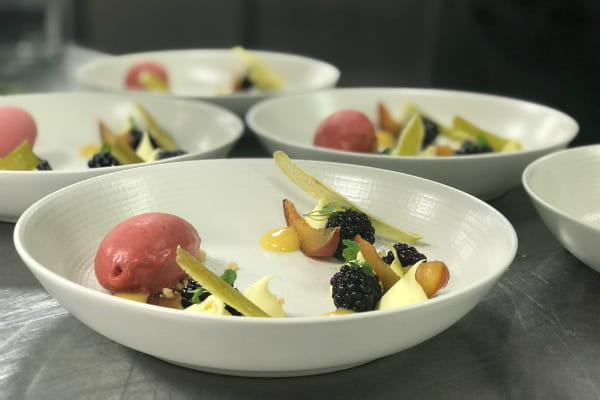 Bowls of apple, plum and blackberry pieces with quenelles of ice cream and big drops of custard
