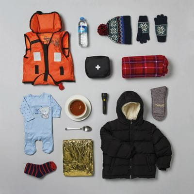 Photograph taken from above showing shopping items laid out neatly on a surface (life-jacket, first aid kit, sleeping bag, warm clothing, water bottle, baby-grow, etc.)